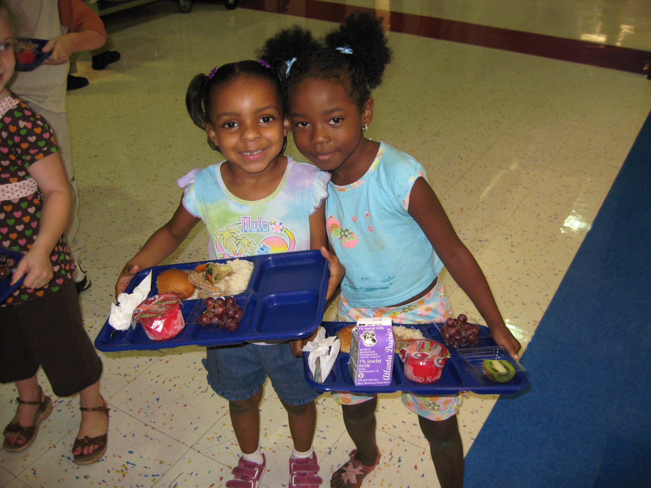 Two little girls holding lunch trays.