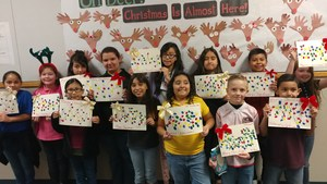 Group of students holding a paper Christmas craft.