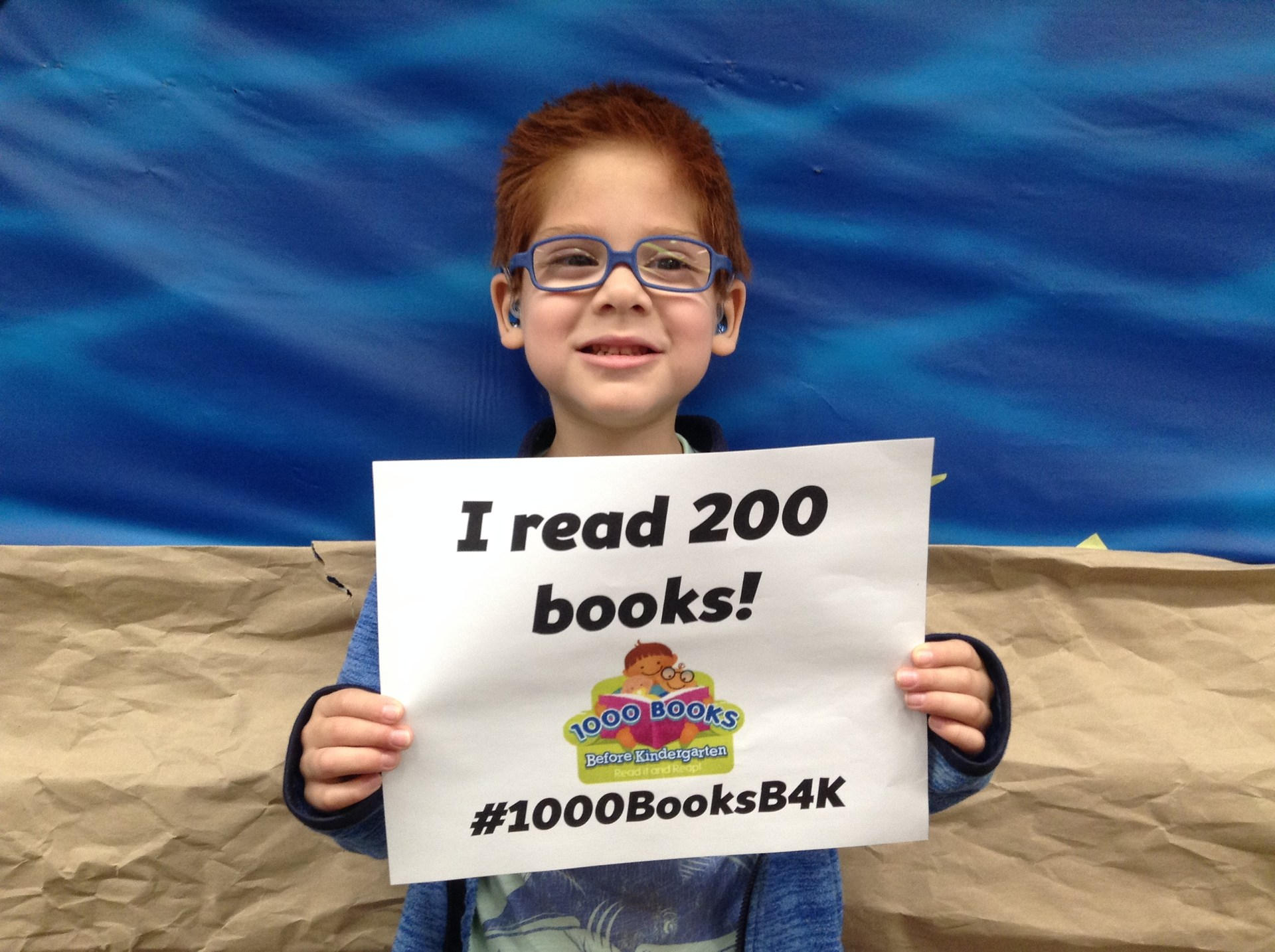 Photo of preschool student holding a sign showing that he has read 200 books.