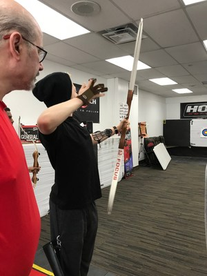 Student taking aim as instructor watches