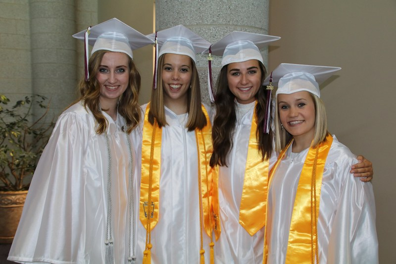 photo of four girls with white gowns and caps on graduation