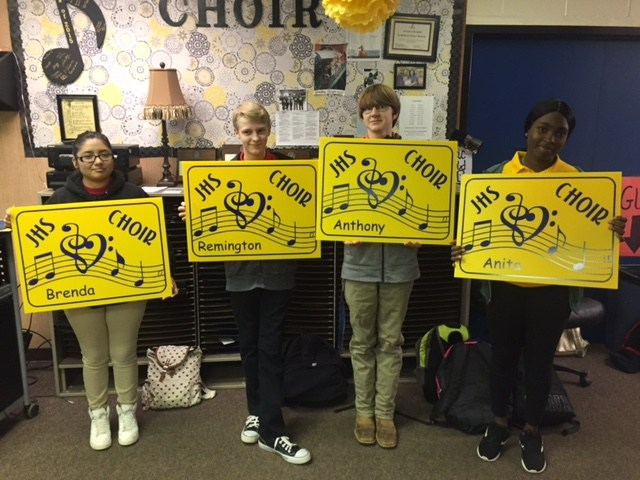 Students with choir yard signs
