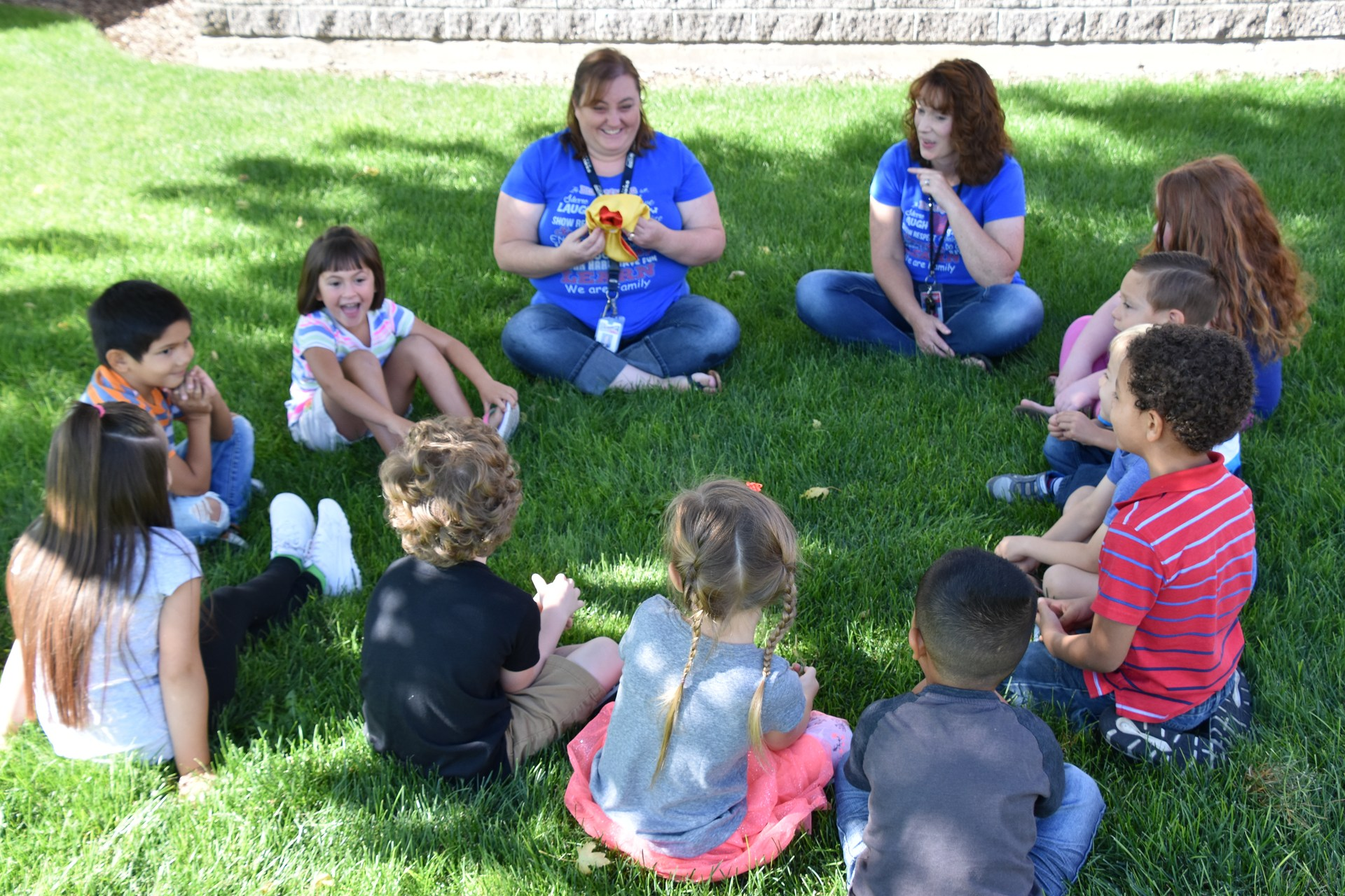 kindergarten students at orientation sitting outside in a circle participating in a get to know each other game.