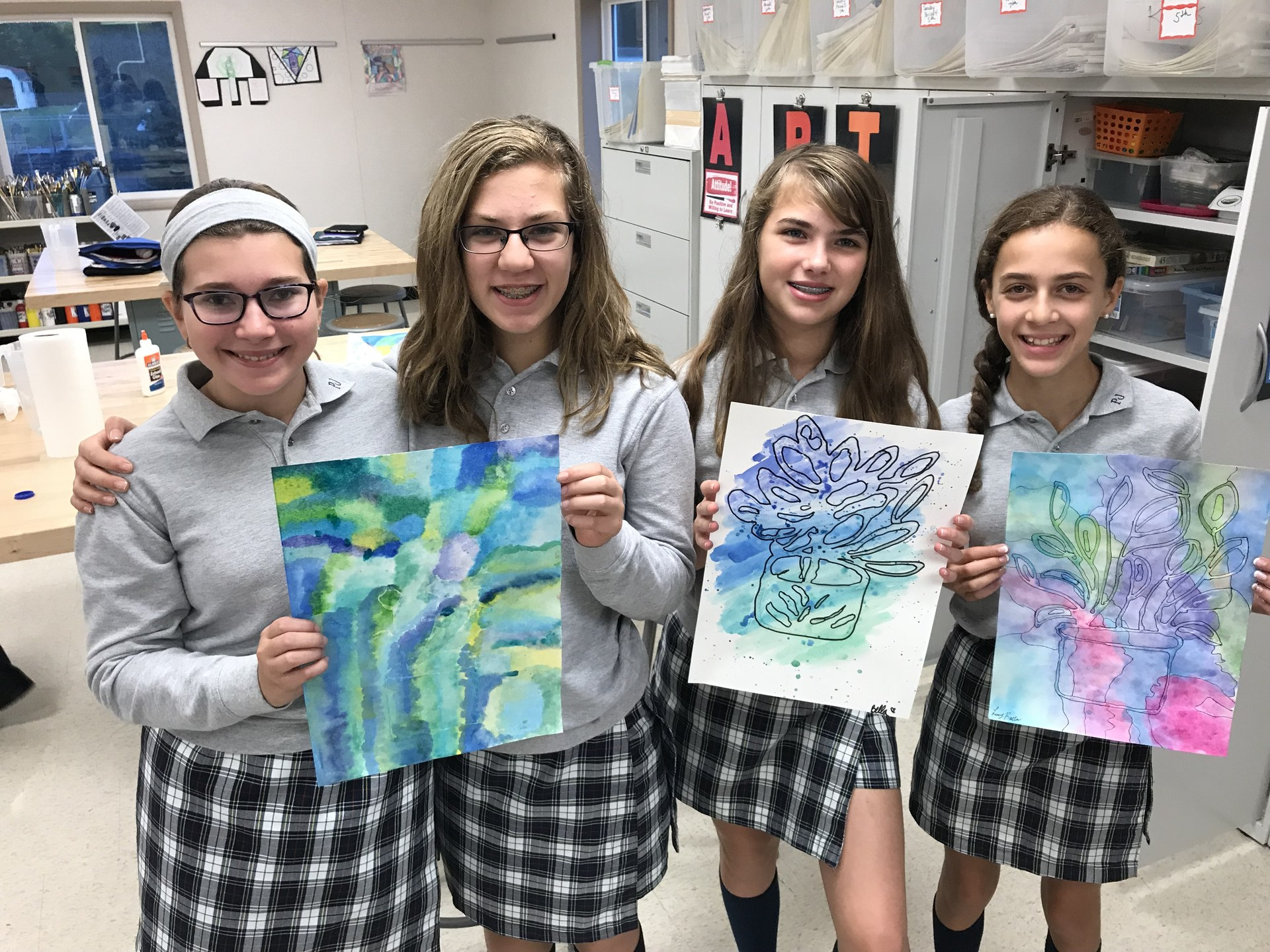 Group of girl students pose with paintings
