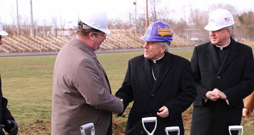 President Tim Hamer shakes hands with Bishop Ronald Gainer