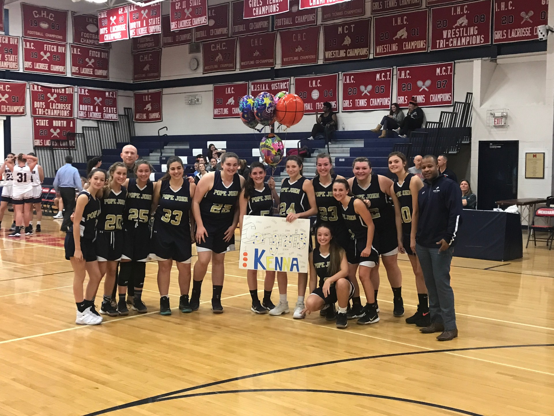 Girls basketball player poses with team after scoring 1,000th career point