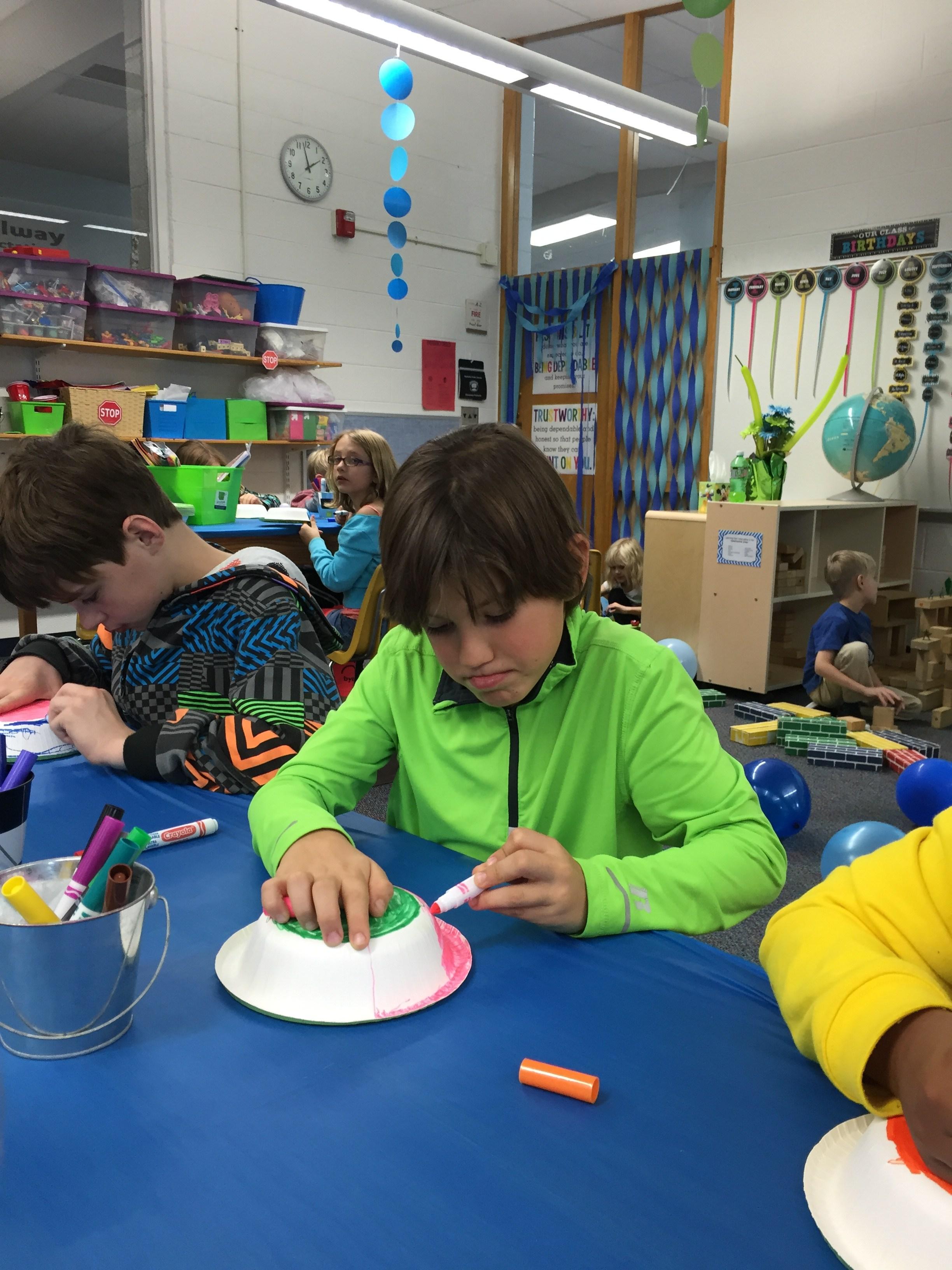 Boy painting a bowl.