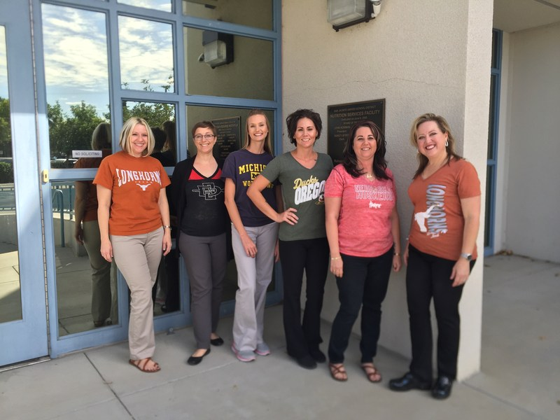 SJUSD Nutrition Services Department staff in front of their building, wearing college gear.