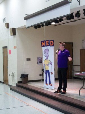 A man is standing on stage beside a poster of a character with the name NED above his head.