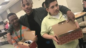 Lancaster High School student poses with two students that he gave news shoes to for Christmas.