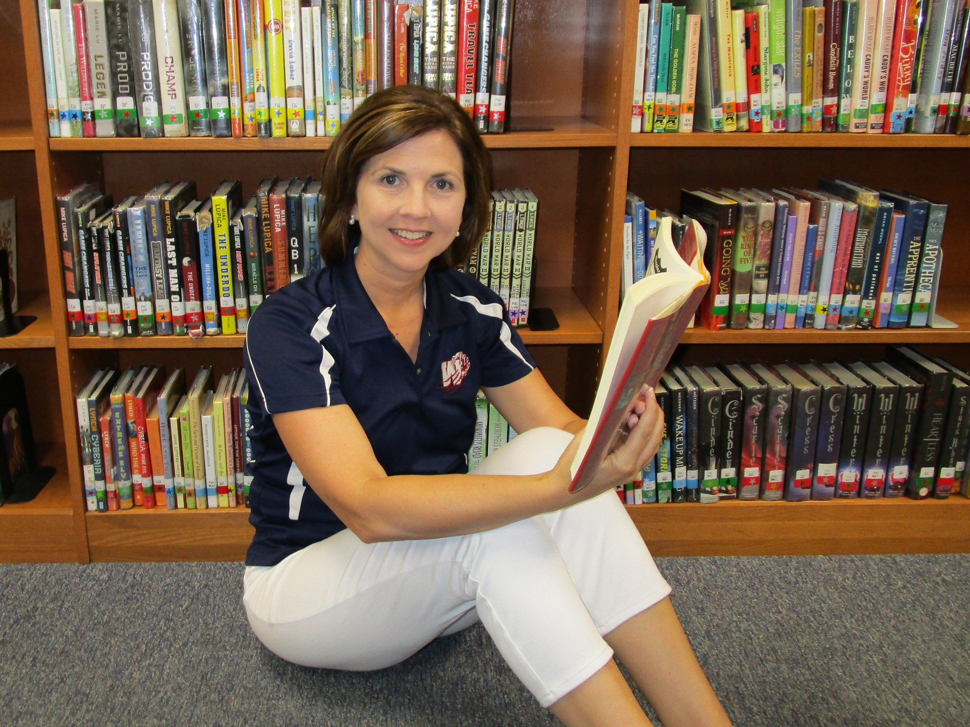 Dr. Mull sits in the media center and enjoys reading.
