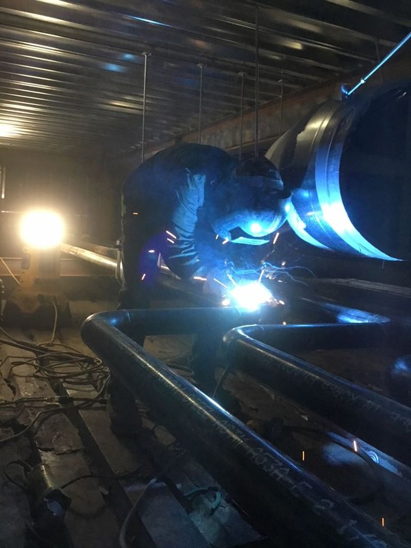 Welders busy working on pipes.