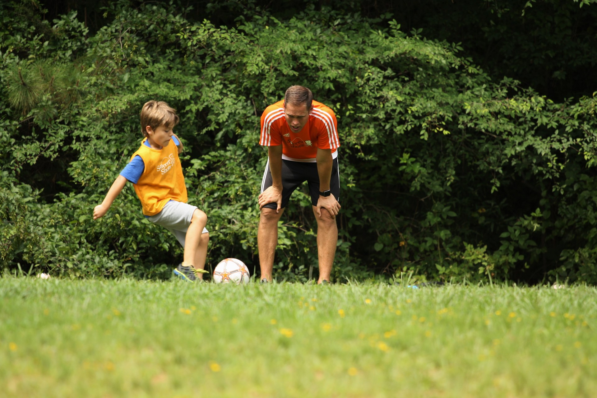 Boy and coach play soccer in green field