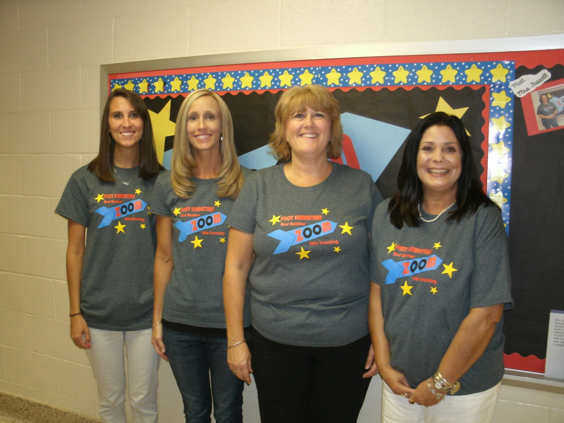 Four first grade teachers are standing in front of a bulletin board.