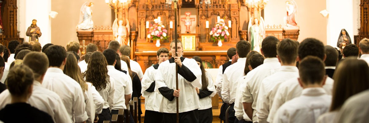 altar servers carry the cross out of the OLSH Chapel after Mass