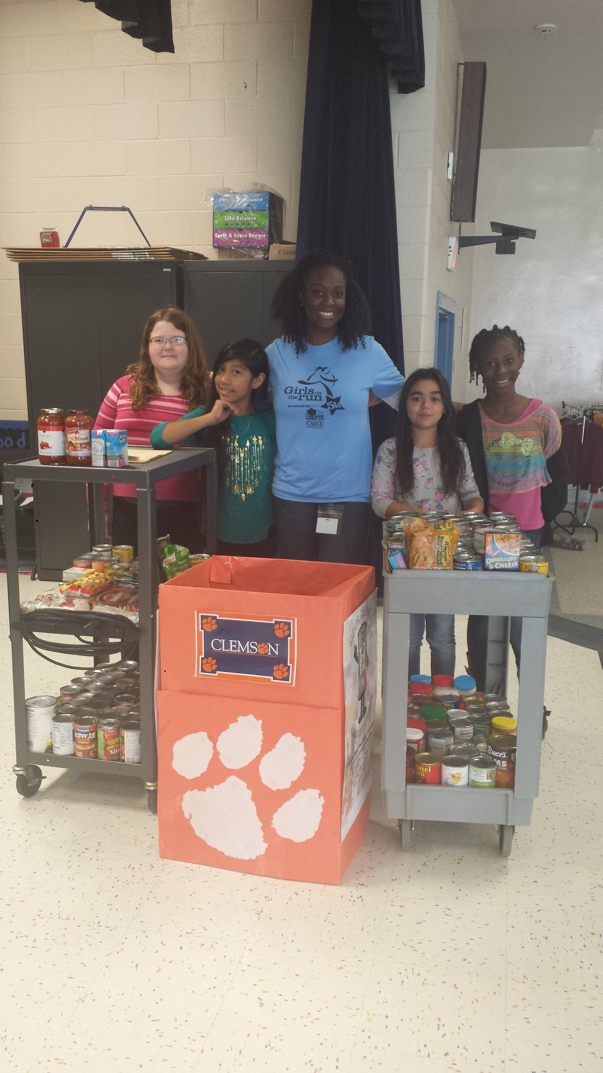 AEP students and Ms. Doyle pause from counting cans during our annual Carolina versus Clemson Canned Food Drive
