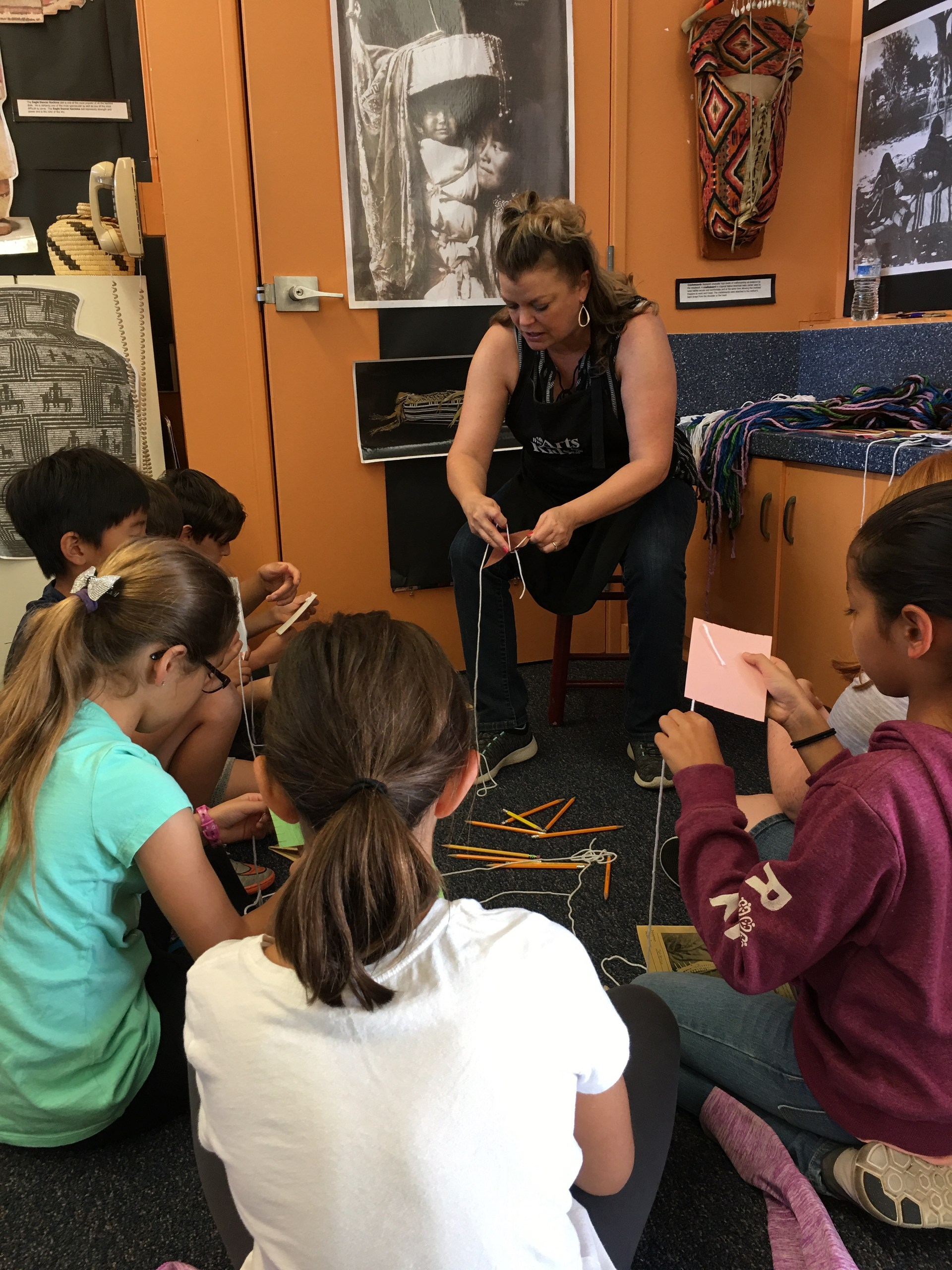 Students watching and artist demonstrate weaving.