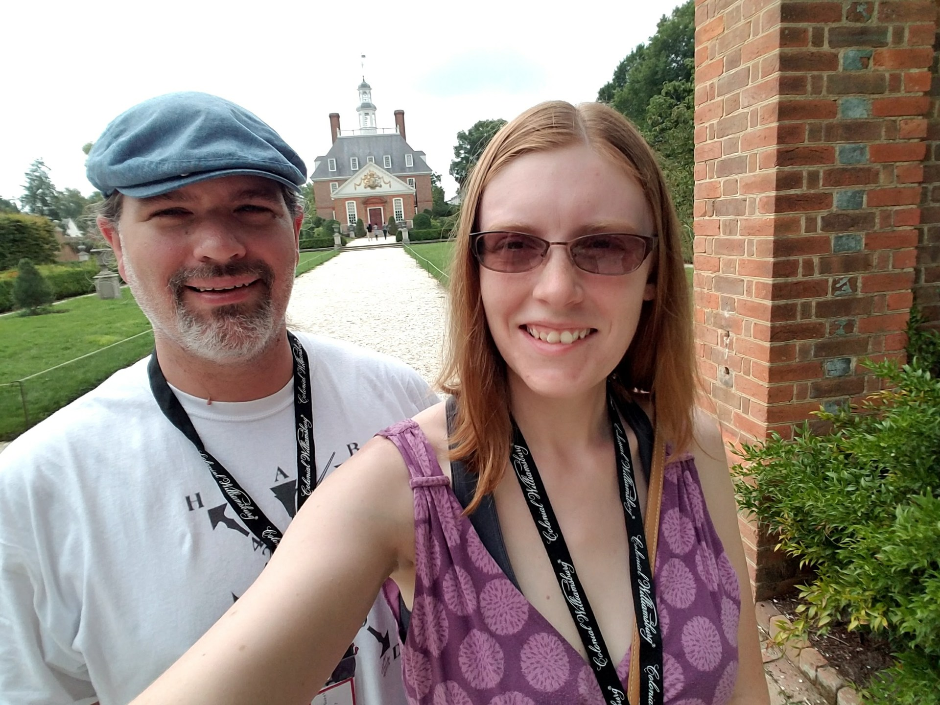 Man with hat and a white and black beard stands next to a woman with strawberry blonde hair and sun glasses with a colonial-style palace in the far background