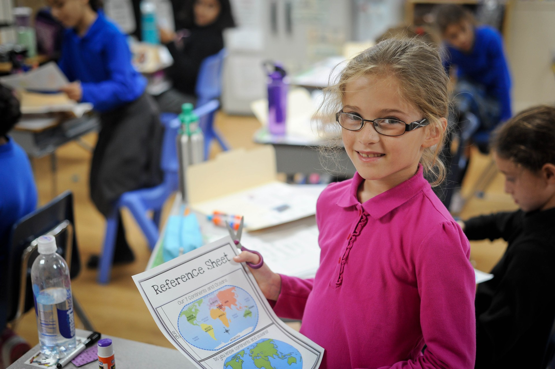 girl holding reference sheet about world map