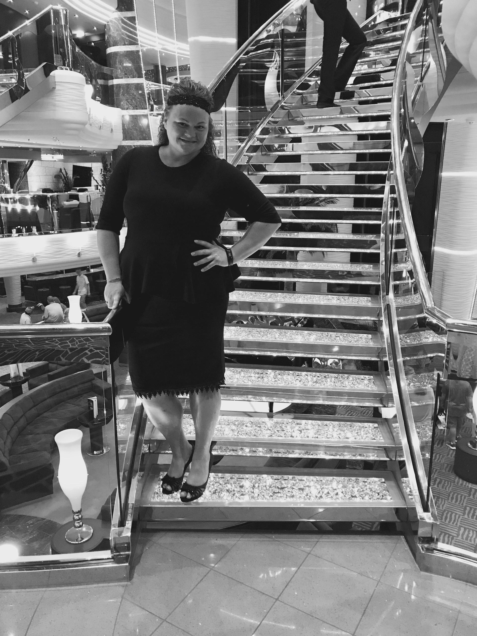 Mrs. Lozoya in a black dress by a crystal staircase.