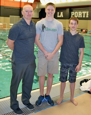 Coach and two dive team students standing beside swimming pool