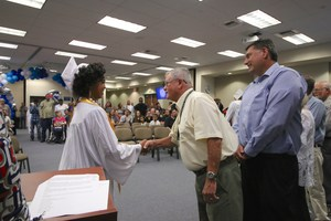 Board President Jim Smith shaking hands with a graduate.