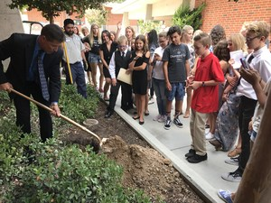 Arroyo Seco Assistant principal Cliff Miller takes his turn putting a shovel full of dirt on the school's time capsule.