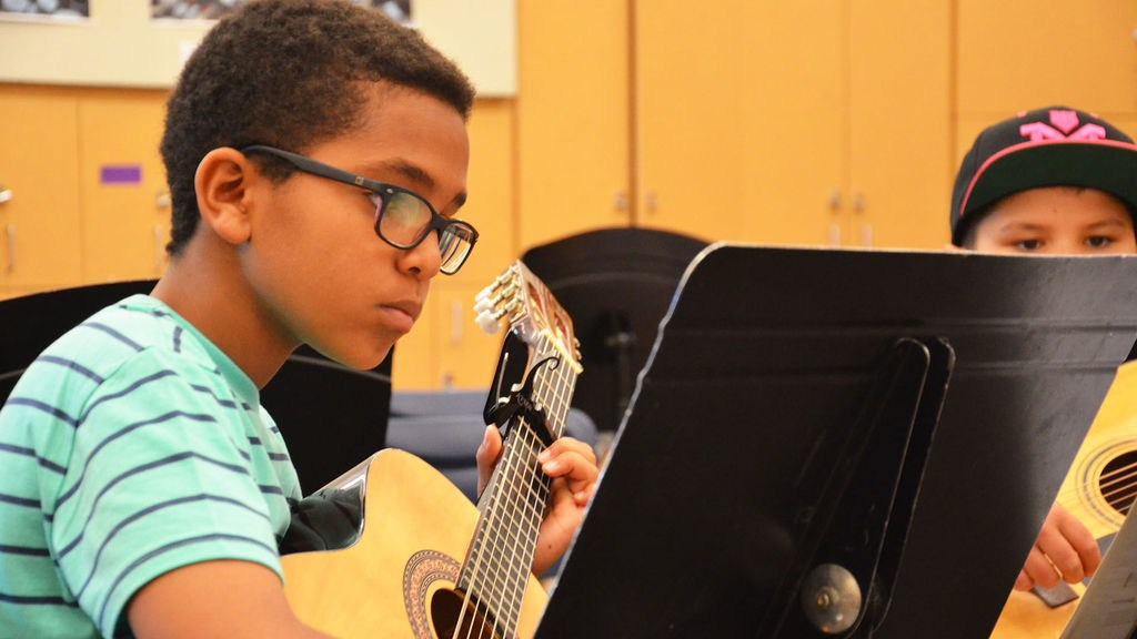 Middle school student reads music while playing guitar