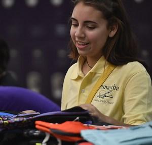 Volunteer helping students pick out backpacks.