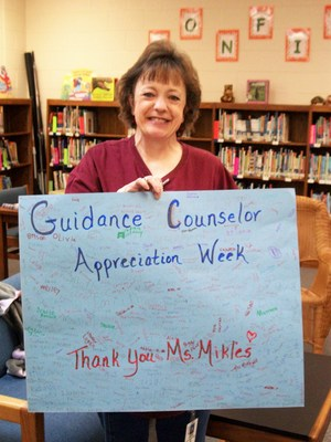 Ms. Mikles holding a card signed by students for Guidance Counselor Appreciation Week.