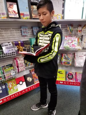 Student holding a book open in front of a shelf with several books on it