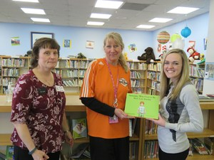 Amanda Eavey (right) and Laurie Ann Curtis present the book donation to McFall Elementary librarian Amy Wandrie.