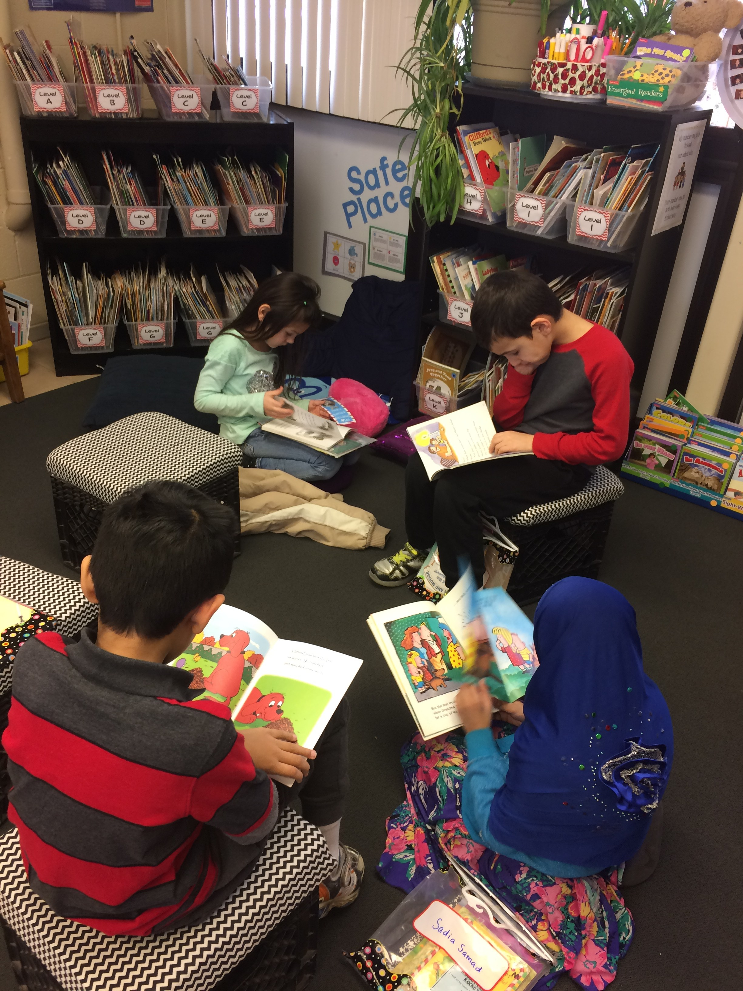 Four students reading in a circle on the floor