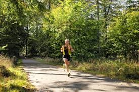 A student athlete running through a forest trail.