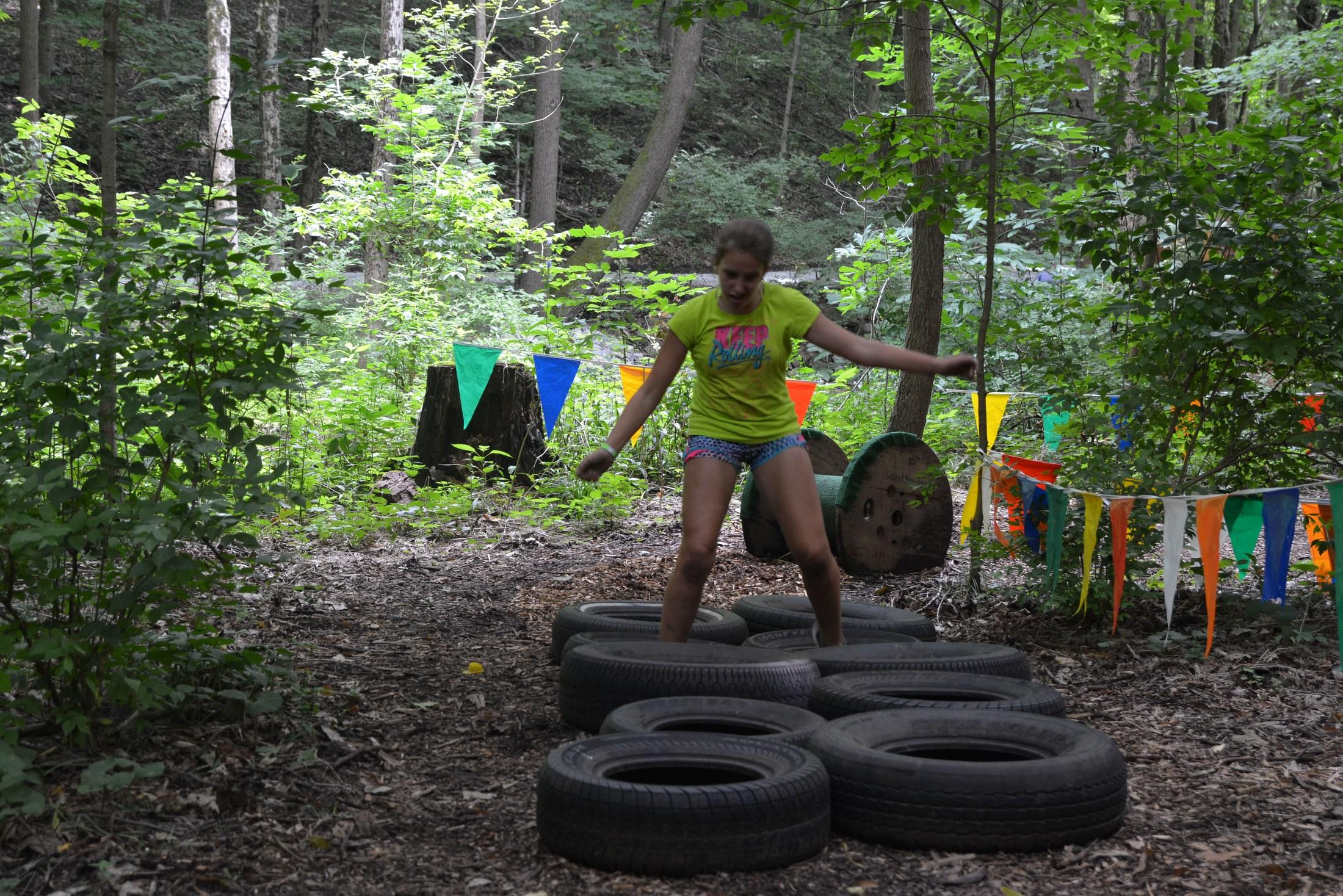 Female student jumping through tires at Camp Willard