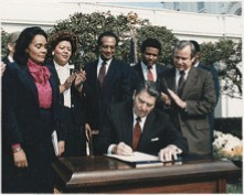 Photo of President Ronald Reagan signing the holiday into law in 1983