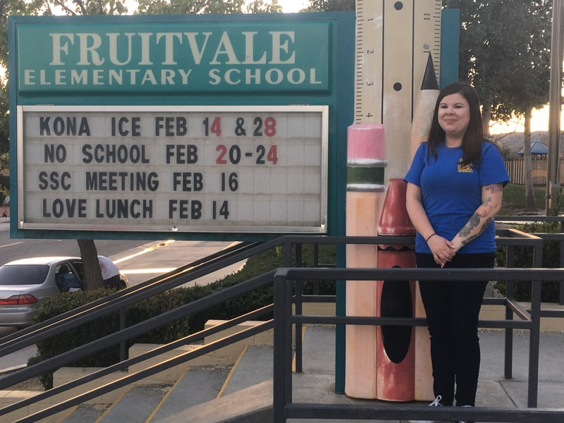Christina Cook in front of a Fruitvale Elementary sign.