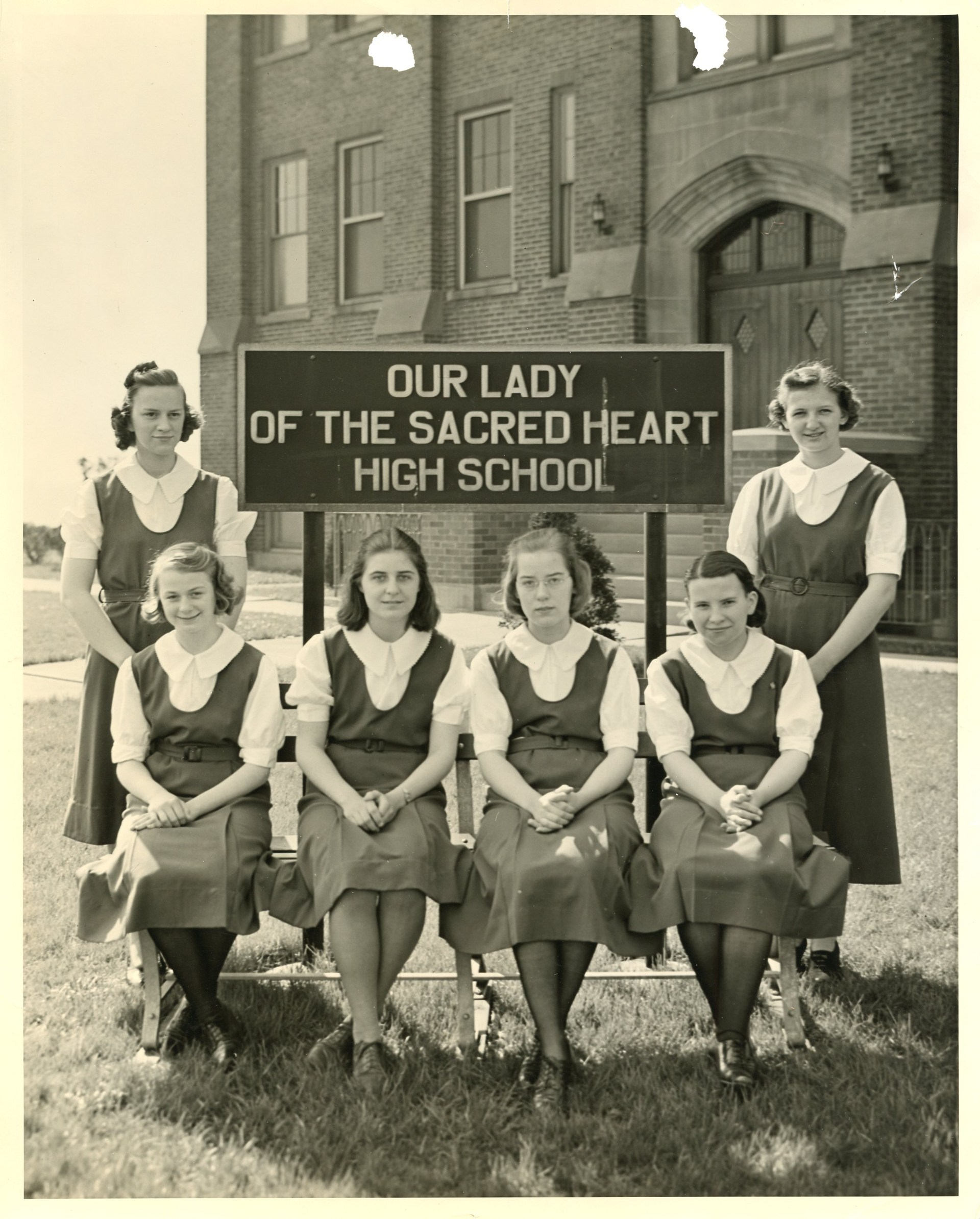 Six young women pose around the Our Lady of the Sacred Heart High School sign