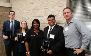 Three DECA students pose with sponsor and advisor