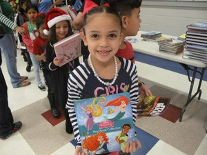 student holding book donated by Molina foundation