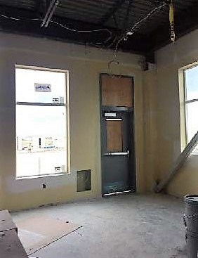 Kindergarten classroom with yellow walls, concrete floors and grey temporary door to the outside