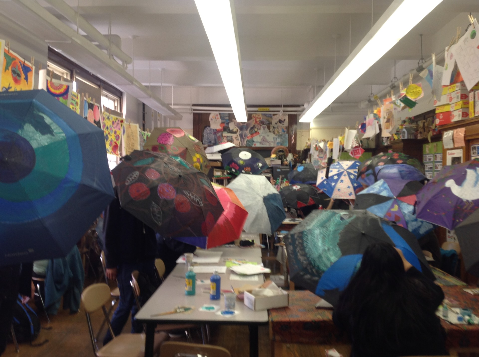 Students painting umbrellas for spring exhibit.