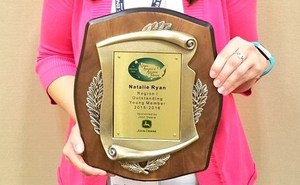 Natalie Ryan posing with her award for national recognition.