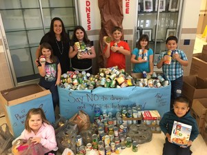 A picture of students and counselor standing by the donated cans of food for the local food pantry.