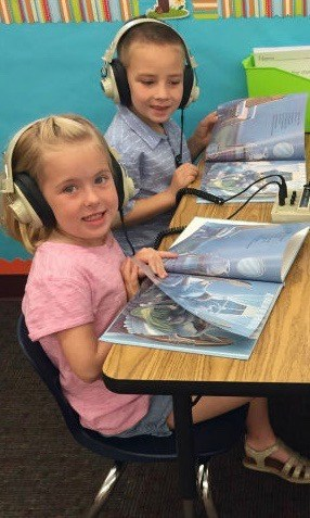 Two kids wearing headphones and reading a book.