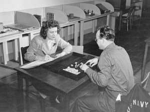 Soldier at a table with evaluator with stopwatch