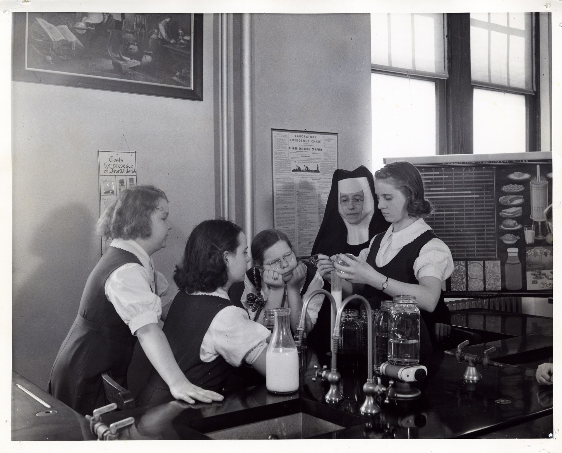 A group of young women learning from a Sister in a science lab