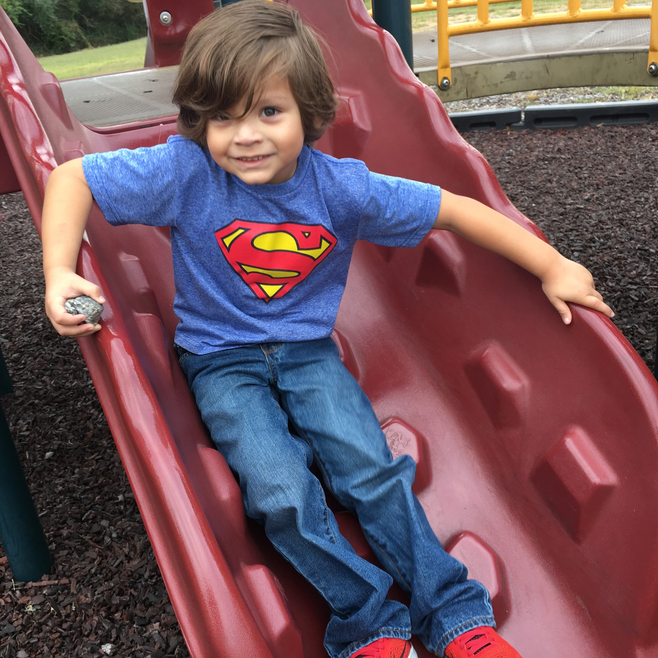 student coming down slide in superman shirt