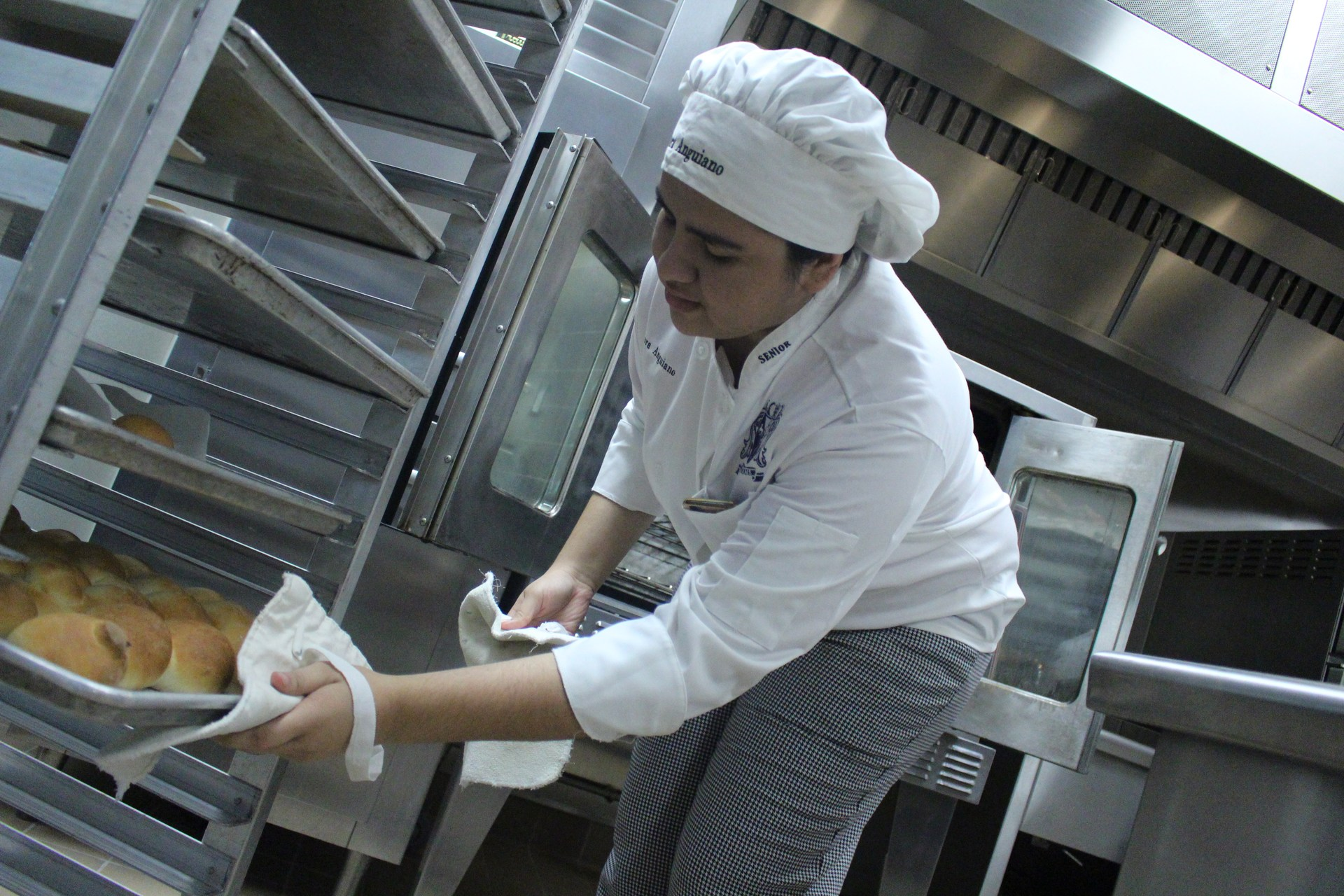 Student removing hot roll pan from the rack