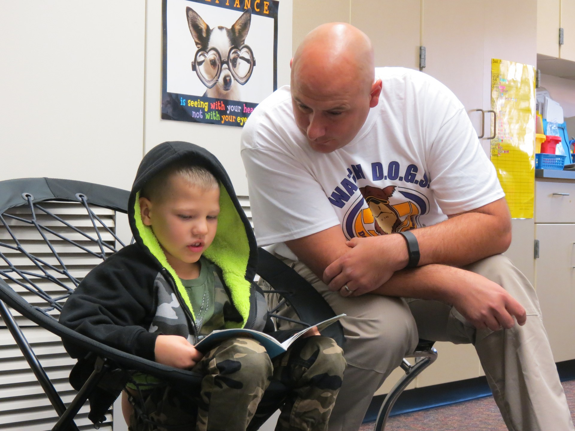 A watchdog reads with a student in class.